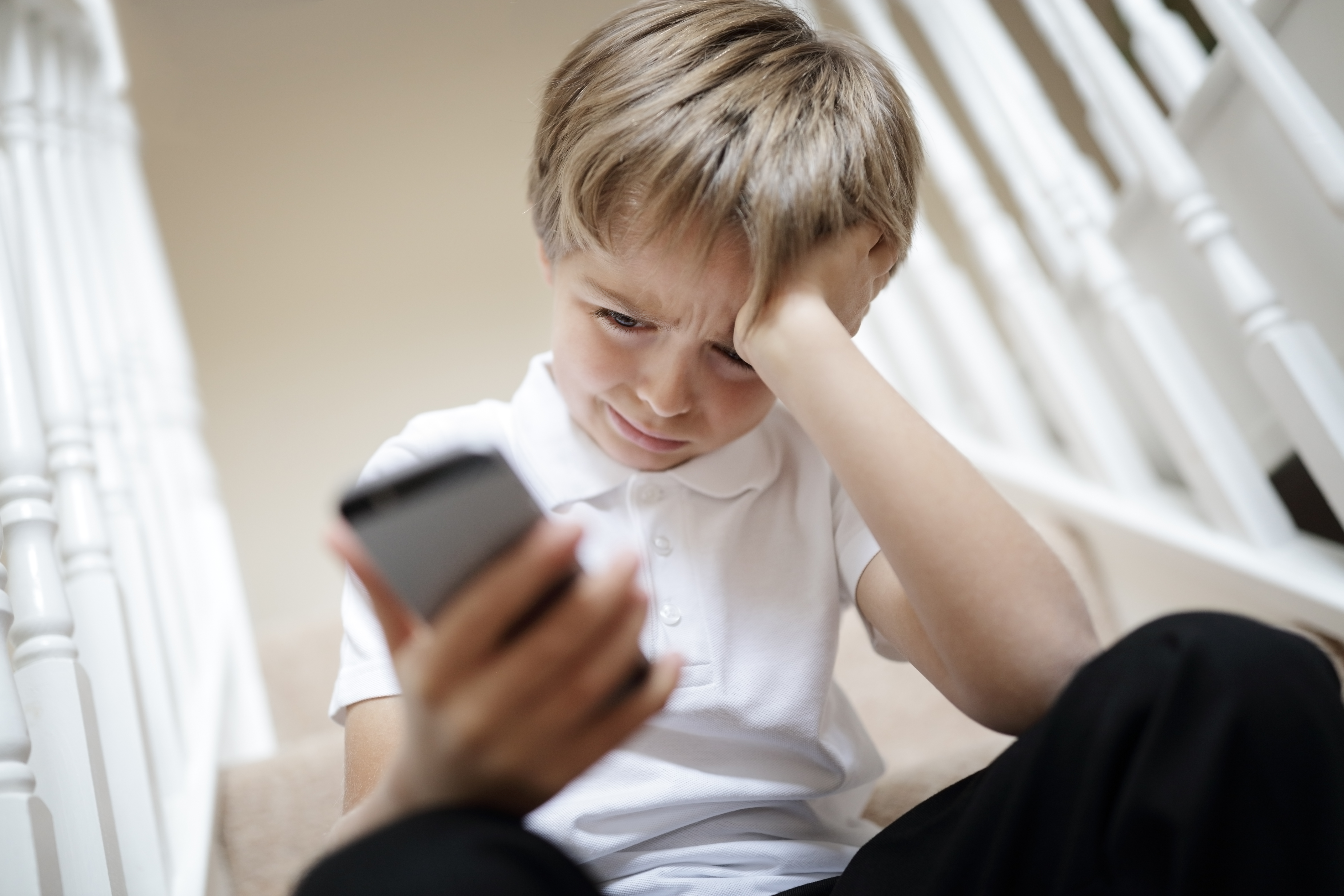 Young boy looking at his phone, very upset by what he sees