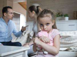 Little girl holding teddy bear while parents fight in background